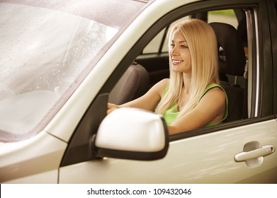 Portrait of beautiful smiling young woman in car.