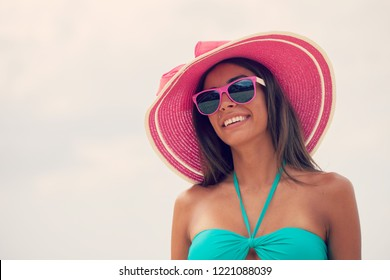 Portrait of a beautiful smiling young woman in bikini and sunhat
