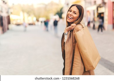 Portrait of beautiful smiling young woman with shopping bags looking back