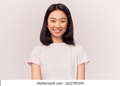 Portrait of beautiful smiling young woman grins at camera, grinning, eyes glistening. Businesslike young woman Asian appearance with black hair brown eyes stands isolated white background in Studio