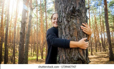 Portrait of beautiful smiling young woman leaning and hugging big old tree in forest. Concept of love, ecology protection and harmony with nature.