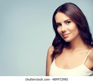 Portrait of beautiful smiling young woman, with blank copyspace area for slogan or text message. Caucasian brunette model in emotional concept studio shoot.