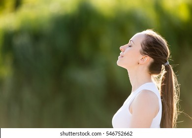 Portrait of beautiful smiling young woman enjoying yoga, relaxing, feeling alive, breathing fresh air, got freedom from work or relations, calm and dreaming with closed eyes, in green park, copy space