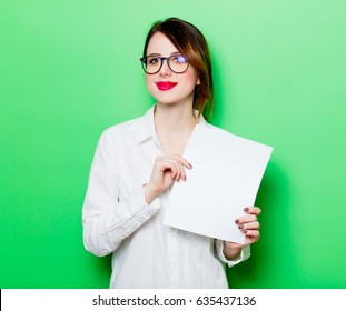 portrait of beautiful smiling young woman holding paper on the wonderful studio green background