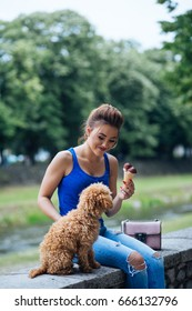 Portrait of beautiful smiling young woman with her little red poodle puppy.