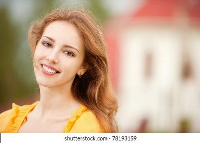 Portrait of beautiful smiling young woman close up on background of big house.