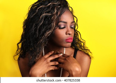Portrait of beautiful South African young woman with curly loose hair and bright red lips wearing color dress over yellow background. Latin woman with makeup, nail polish and hairstyle. black woman.