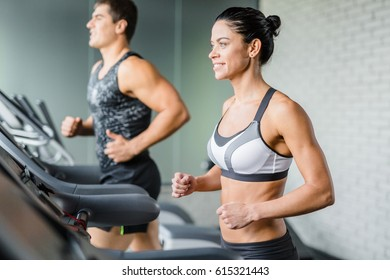 Portrait of beautiful   sportive brunette woman smiling while exercising on treadmill in gym next to fit man