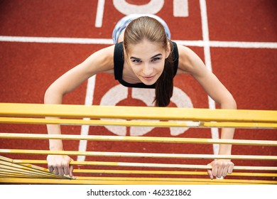 Portrait of a beautiful sports woman doing stretching exercise on outdoor stadium