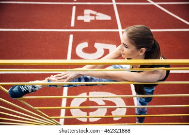 Portrait of a beautiful sports woman stretching legs on outdoor stadium