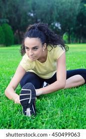 Portrait of beautiful sportswoman stretching on grass in park.Bokeh