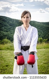 Portrait of beautiful sporty female wearing karate kimono and red gloves in nature. Martial arts.