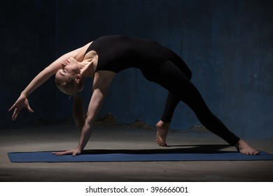 Portrait of beautiful sporty fit young woman in black sportswear working out indoors against grunge dark blue wall. Model standing in Camatkarasana, Wild Thing or Flip-the-Dog posture. Full length.
