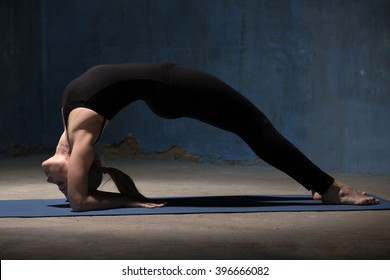 Portrait of beautiful sporty fit young woman in black sportswear working out indoors against grunge dark blue wall. Model standing in Bridge pose, Two-Legged Inverted Staff yoga Posture. Full length