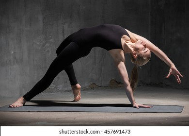 Portrait of beautiful sporty fit young woman in black sportswear working out indoors against grunge dark grey wall. Model standing in Camatkarasana, Wild Thing or Flip-the-Dog posture. Full length.