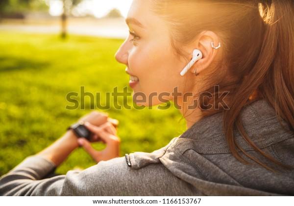 Portrait von schöner sportlicher Frau 20er in Sportbekleidung mit smarter Armbanduhr und drahtlosem Oarbud während der Erholung im grünen Park