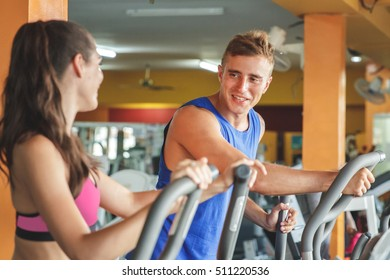 portrait of beautiful sporty woman exercising on fitness machine and talk with her partner