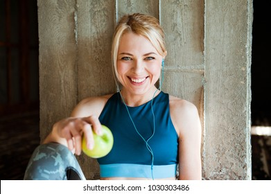 Portrait of beautiful sporty woman in headphones with Apple after workout.