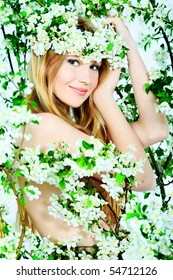 Portrait of a beautiful spring girl in apple tree flowers.