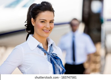 Portrait of beautiful stewardesses smiling with pilot and private jet in background at terminal