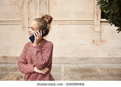 Portrait beautiful student girl in college campus with stone building, smiling smartphone call conversation, speaking on phone outdoors. Teenager female using technology, leisure recreation lifestyle.