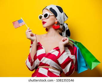Portrait of beautiful style woman in sunglasses and striped clothes with US flag and shopping bags on yellow background