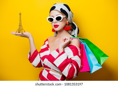 Portrait of beautiful style woman in sunglasses and striped clothes with Eiffel tower statue and shopping bags on yellow background