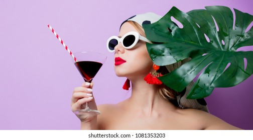 Portrait of beautiful style woman in sunglasses with palm leaf and cocktail on purple background