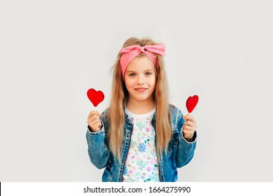 Portrait of a beautiful stylish fashionable girl in glasses, with a heart-shaped lollipop, on a white background, free time summer vacation