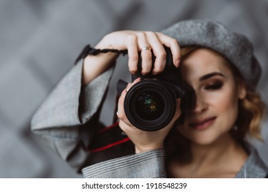 Portrait of a beautiful stylish woman photographer in a gray outfit with a camera in her hands in a photo studio. Soft selective focus. Copy space.