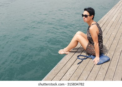 Portrait of beautiful stylish woman relaxing after active walking while sitting on a wooden pier with copy space in a summer day, young female tourist enjoying rest and good weather during her weekend