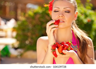portrait of a beautiful Summer Woman on vacation with strawberry in her hands