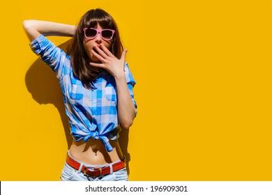 retrato de uma bela menina surpreendida em camisa azul e óculos em um fundo de parede laranja
