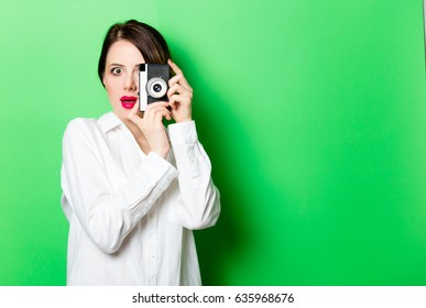 portrait of beautiful surprised young woman with retro camera on the wonderful studio green background