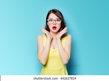 portrait of beautiful surprised young woman in glasses on the wonderful blue studio background