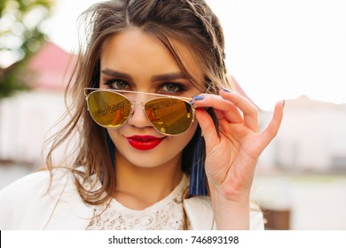 Portrait of beautiful and sweet girl with perfect makeup and red lips, holding sunglasses and looking at camera. Fashionable and stylish woman wearing in white,walking after beauty salon.Street style.
