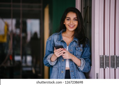 Portrait of a beautiful, tall, elegant and young Indian Asian woman texting on her smartphone. She is wearing a retro denim jacket with an 80's feel and is smiling happily.