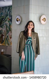 Portrait of a beautiful, tall, slim and attractive Indian Asia woman in a striped jumpsuit and a green jacket over her shoulders. She is elegant, confident and smiling as she leans against a wall.