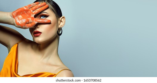 Portrait of a beautiful tanned fashionable girl with bright makeup in orange colors and wet dark hair.