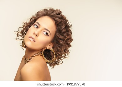 Portrait of a beautiful tanned girl with fine curls and elegant makeup with arrows posing in gold jewelry. Light beige background with copy space. Jewelry and beauty.