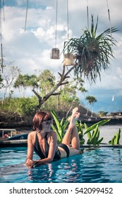 Portrait of beautiful tanned woman in black swimwear relaxing in swimming pool spa. Hot summer day and bright sunny light. Beautiful ocean, sky and asian plants on the background. Tropical island Bali
