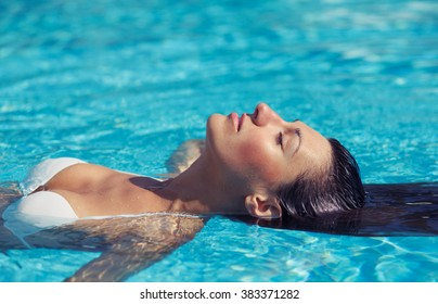 Portrait of beautiful tanned woman in white swimwear relaxing in swimming pool spa. Hot summer day and bright sunny light.