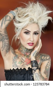 Portrait of beautiful tattooed woman with hand in hair