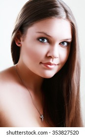 Portrait of beautiful teen girl with perfect skin smiling over grey background