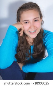 Portrait of a beautiful teenage girl with braces smiling wearing turquoise blouse