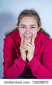 Portrait of a beautiful teenage girl with braces smiling wearing red hoodie blouse