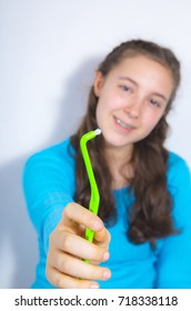 Portrait of a beautiful teenage girl with braces smiling wearing turquoise blouse and showing special braces toothbrush