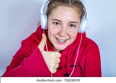 Portrait of a beautiful teenage girl with braces and headphones smiling wearing red hoodie blouse