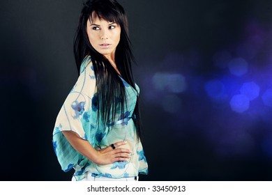 Portrait of a beautiful teenage girl over blue background with lights
