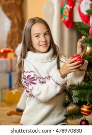 Portrait of beautiful teenage girl posing at Christmas tree with red bauble